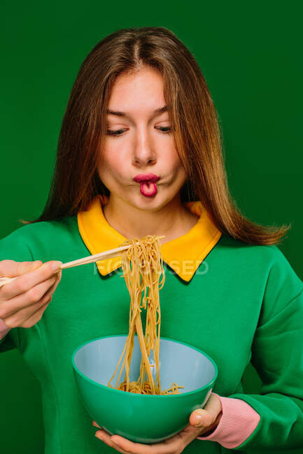 Positive young female in green shirt looking at camera grimacing making fish mouth while eating yummy instant noodles with chopsticks on green background — Stock Photo