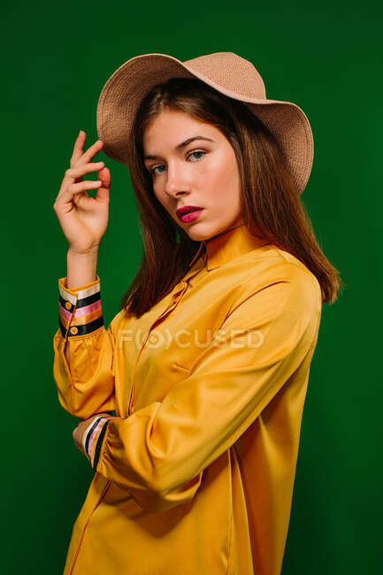 Side view of trendy confident millennial female in colorful clothes and hat looking at camera against green background — Stock Photo