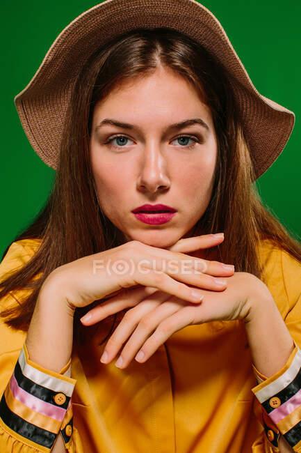 Mujer millennial de confianza de moda en ropa colorida y sombrero mirando a la cámara apoyada en la mano contra el fondo verde - foto de stock