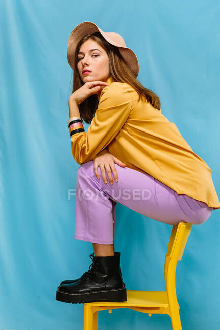 Side view of trendy confident millennial female in colorful clothes and hat sitting on stool and looking at camera against blue background — Stock Photo