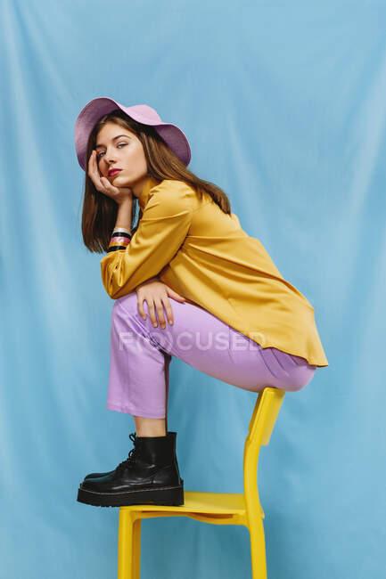 Vista lateral da fêmea millennial confiante na moda em roupas coloridas e chapéu sentado no banquinho e olhando para a câmera contra o fundo azul — Fotografia de Stock