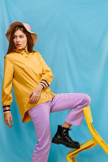 Бічний погляд на вродливу молоду впевнену жінку в стилізованому барвистому вбранні і капелюсі, що дивиться геть, стоячи крутою ногою на жовтому стільці на синьому тлі. — стокове фото