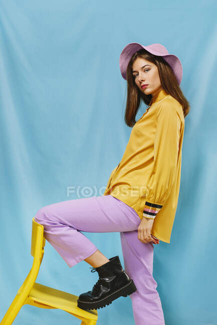 Side view of trendy young confident female in stylish colorful wear and hat looking at camera while standing steeping foot on yellow chair against blue background — Stock Photo