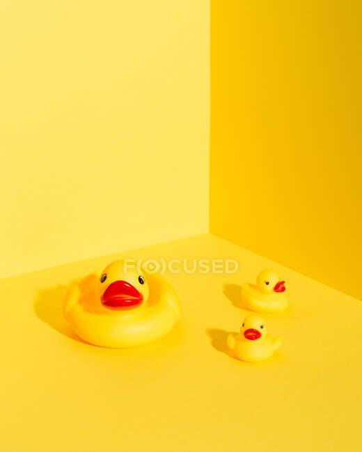 Von oben eine Reihe niedlicher Gummientchen und Entenmama-Spielzeuge auf leuchtend gelbem Hintergrund — Stockfoto