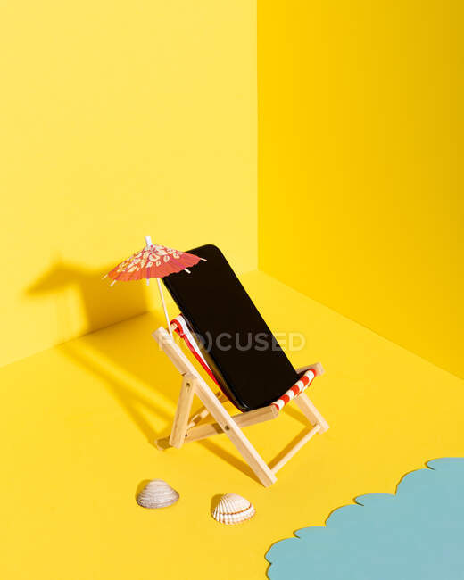 From above composition of miniature deckchair with parasol and mobile phone placed near blue sea against yellow background — Stock Photo