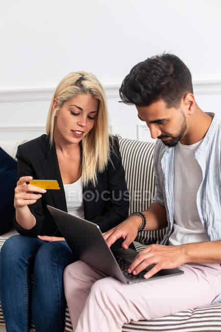 Блондинка улыбается и читает удостоверения кредитной карты веселому этническому парню с ноутбуком, сидя на диване и делая онлайн покупки вместе — стоковое фото