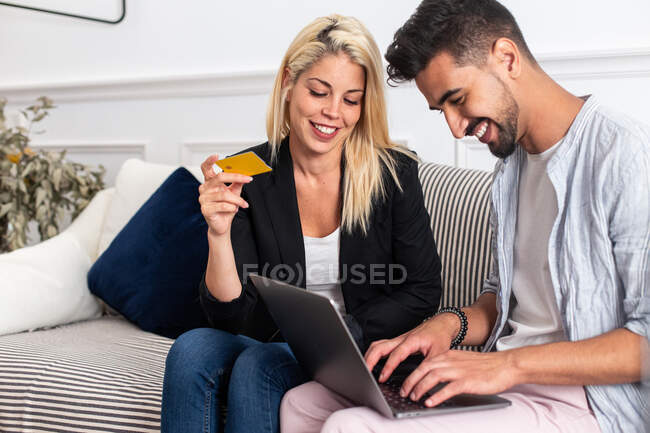 Delighted blonde female smiling and reading credit card credentials to cheerful ethnic boyfriend with laptop while sitting on sofa and making online purchases together — Stock Photo