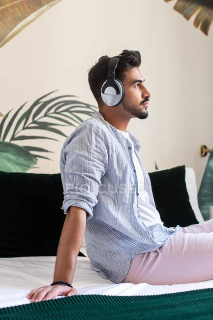 Vue latérale d'un homme hispanique barbu réfléchi assis sur son lit et jouissant d'une bonne musique à la maison — Photo de stock