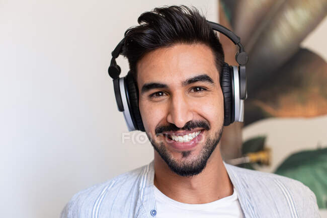 Happy ethnic guy in headphones smiling and looking at camera while listening to music at home — Stock Photo