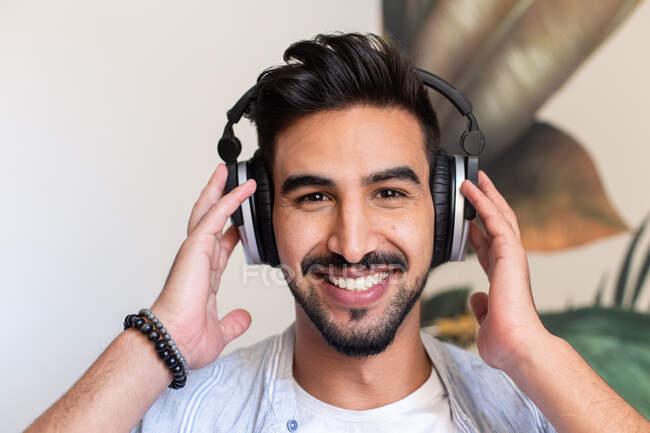 Heureux mec ethnique dans un casque souriant et regardant la caméra tout en écoutant de la musique à la maison — Photo de stock
