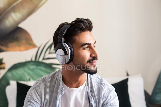 Heureux mec ethnique dans les écouteurs souriant et regardant loin tout en écoutant de la musique à la maison — Photo de stock