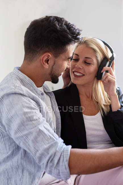 Cheerful woman in headphones smiling and trying to kiss ethnic boyfriend while listening to music at home together — Stock Photo