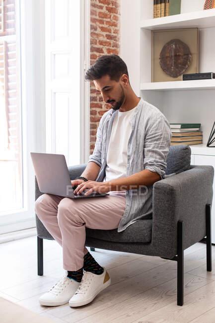 Barbudo hombre étnico utilizando el ordenador portátil mientras se trabaja en el proyecto remoto en casa - foto de stock