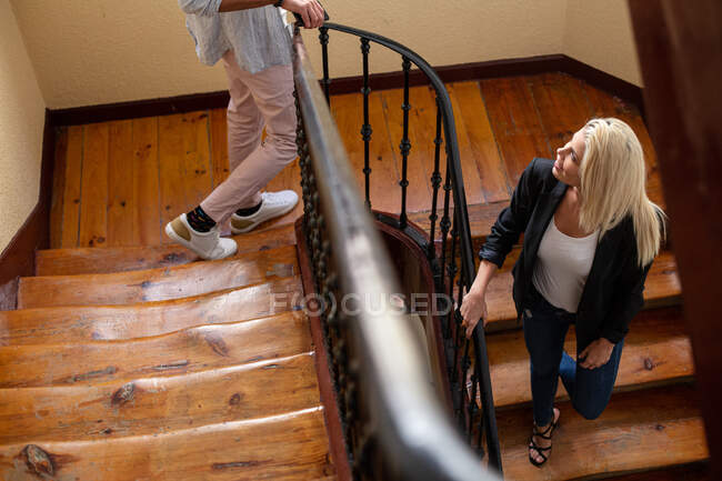 From above blonde female smiling and communicating with crop anonymous boyfriend while walking down wooden staircase at home together — Stock Photo