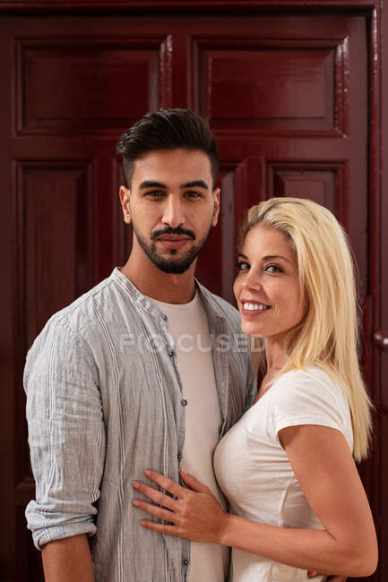 Positive diverse man and woman hugging each other and looking at camera while standing against flat door — Stock Photo