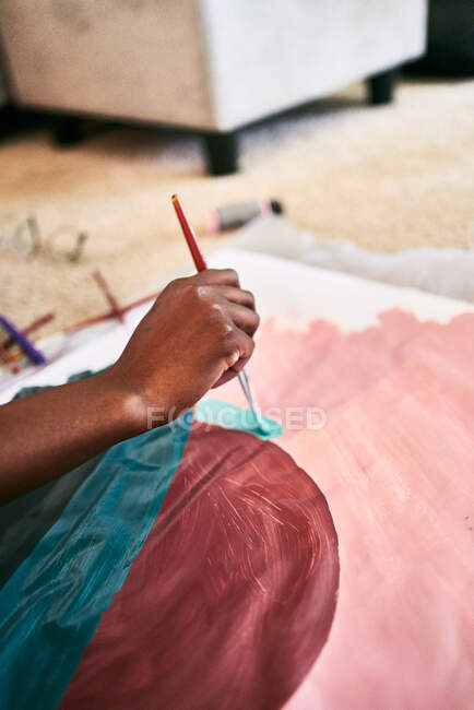 From above of crop anonymous black female with paintbrush drawing colorful picture on paper while sitting on floor at home — Stock Photo