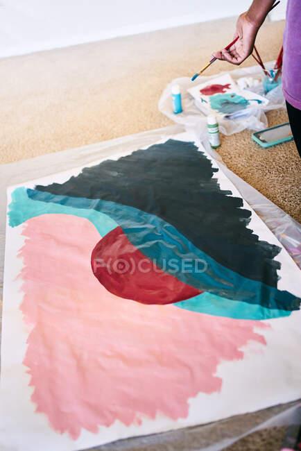 Сверху анонимная черная женщина с кистью, рисующая красочную картину на бумаге, сидя дома на полу — стоковое фото