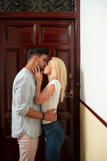 Positif diversifié homme et femme embrassant et regardant les uns les autres tout en se tenant contre porte plate — Photo de stock
