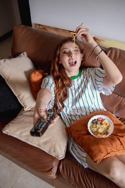 Dall'alto giovane rossa che mangia ramen e cambia canale in TV mentre è seduta sul divano durante il pranzo a casa — Foto stock