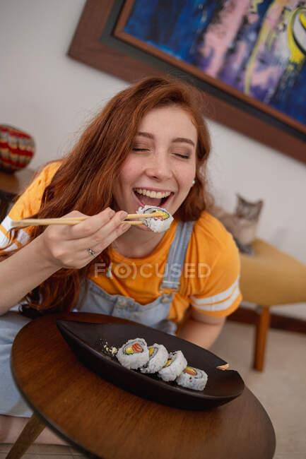Сверху молодая рыжая женщина в повседневной одежде палочками для еды, сидя за столом и поедая суши дома. — стоковое фото