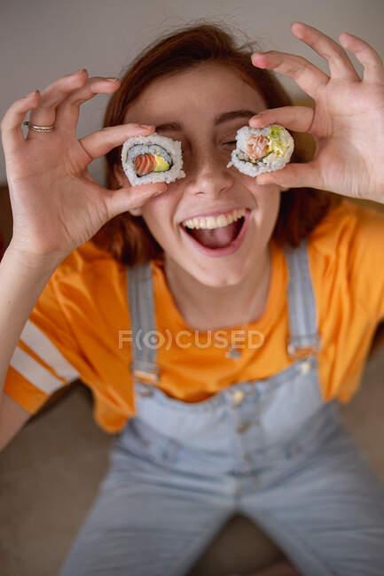 Зверху приємна молода самиця тримає смачний суші біля очей під час обіду вдома. — стокове фото