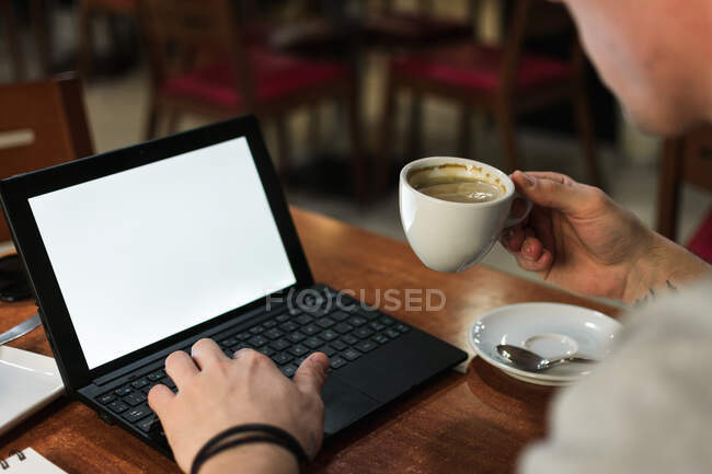 Freelancer sitting at cafe table and browsing laptop — Stock Photo