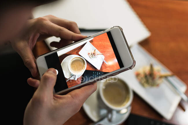 From above anonymous young man using smartphone to take picture of cup of coffee and delicious salad in cafe — Stock Photo