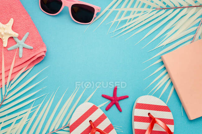 Top view composition of sunglasses and flip flops placed with beach towel and notebook on blue background with palm leaves and starfish representing summer vacation on beach — Stock Photo