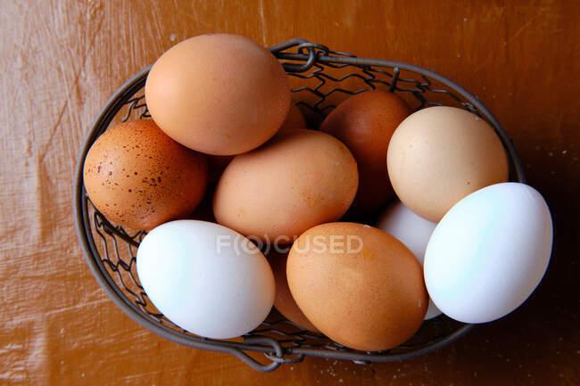 Vue du dessus du panier en métal avec des œufs de poulet frais placés sur la table dans la cuisine — Photo de stock