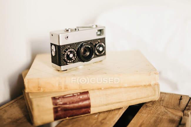 Винтажная фотокамера и стопка старых книг, размещенных на деревянной коробке — стоковое фото