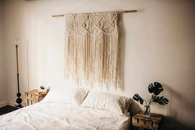 Vintage macrame decoration hanging on wall over comfortable bed in cozy bedroom at home — Stock Photo