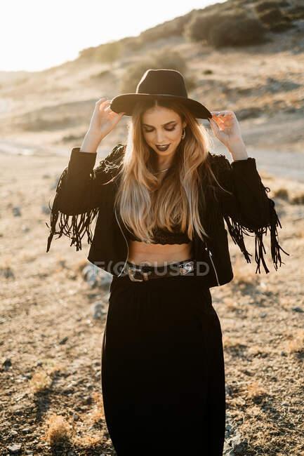 Schlanke Dame im trendigen schwarzen Country-Outfit, lächelnd und mit verstellbarem Hut bei sonnigem Wetter im hügeligen Gelände — Stockfoto