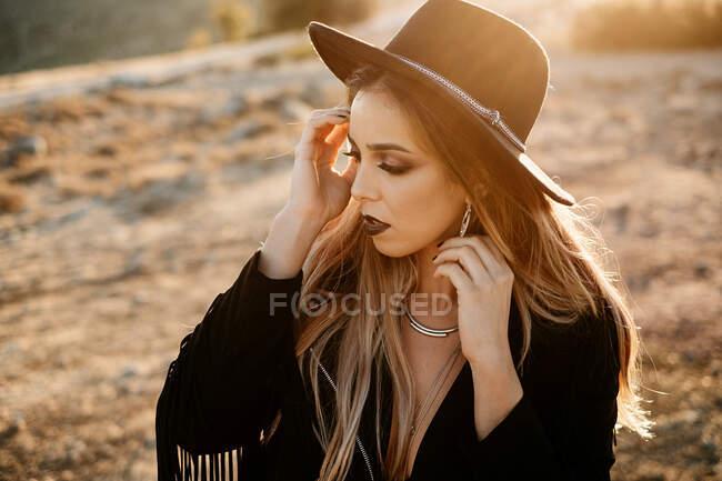 Stilvolle Frau steht auf Felsen im Grünen — Stockfoto