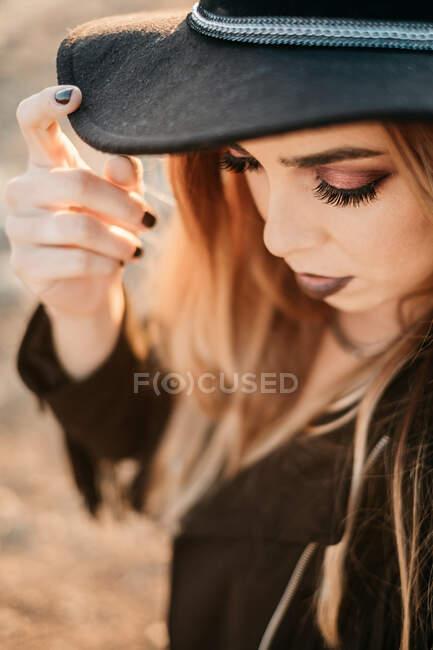 Традиционная дама трогает шляпу и смотрит вниз — стоковое фото