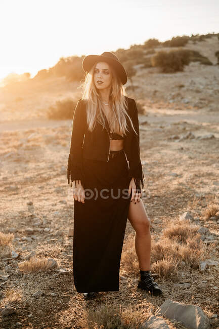 Stylish woman standing on rock in countryside — Stock Photo