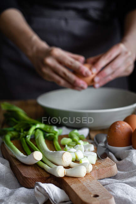 Cropped woman hands breaking eggs in a bowl with bunch of fresh scallions and mushrooms placed on cutting board near poppy seeds — Stock Photo