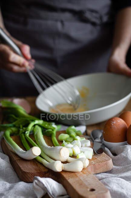 Bando de cebolinhas frescas e cogumelos colocados na tábua de corte perto de ovos e sementes de papoula contra a dona de casa da colheita misturando ingredientes na tigela — Fotografia de Stock