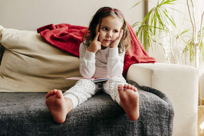 Cute little girl sitting on the couch with a notebook looking for inspiration — Stock Photo