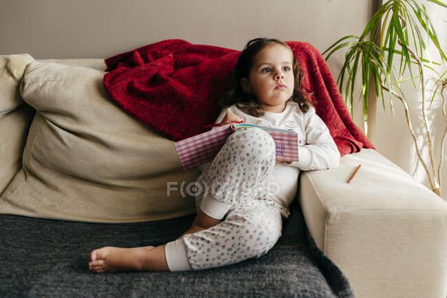 Jolie petite fille assise sur le canapé avec un cahier à la recherche d'inspiration — Photo de stock