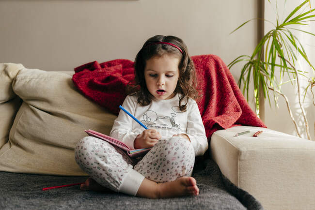Мила дівчинка сидить на дивані і малює в зошиті. — стокове фото
