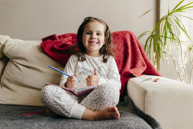 Милая маленькая девочка сидит и улыбается на диване с блокнотом — стоковое фото