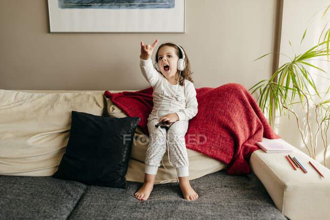 Menina bonito sentado no sofá ouvir música com fones de ouvido — Fotografia de Stock