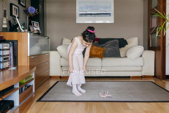 Jolie petite fille en justaucorps rose clair et collants portant une jupe tout en se tenant près de chaussures de danse dans le salon confortable à la maison — Photo de stock