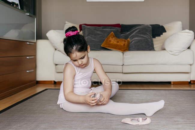 Бічний вид на гарненьку дівчину на горищі сидячи на підлозі біля дивана і одягаючи танцювальні черевики перед репетицією на балеті вдома. — стокове фото