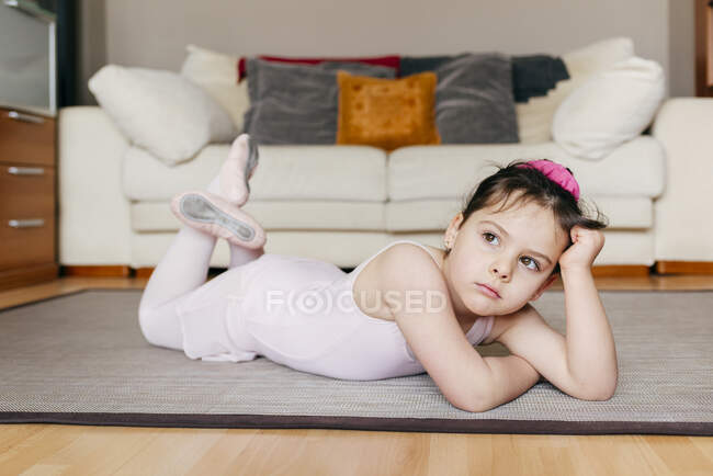 Aburrida niña reflexiva en maillot tirada en el suelo mirando hacia otro lado mientras descansa durante el ensayo de ballet en casa - foto de stock
