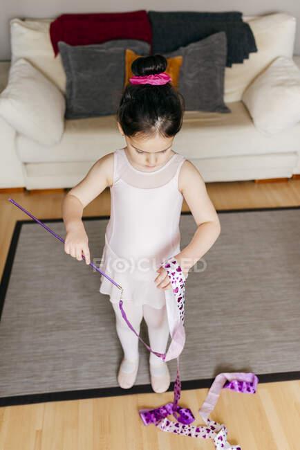 З вище сфокусованої милою дівчинкою в лотатку і цицьки прядуть стрічку під час тренування ритмічної гімнастики в затишній вітальні вдома. — стокове фото