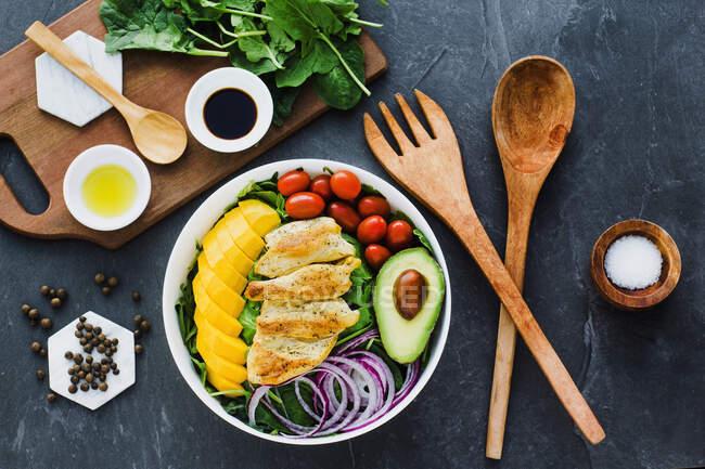 Draufsicht auf gebratenes Huhn und geschnittene Mango in der Nähe von Kirschtomaten und die Hälfte der Avocado auf Spinatblättern und Zwiebeln auf grauem Marmortisch in der Nähe von Geschirr und Soßen mit Gewürzen — Stockfoto