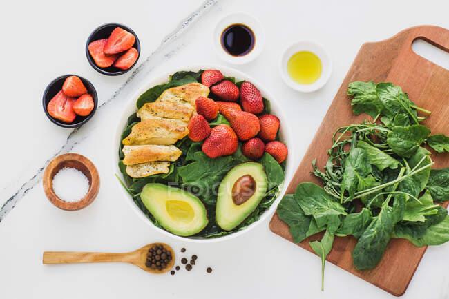 Верхний вид жареного цыпленка и клубники, помещенных около половинки авокадо на шпинат оставить на мраморном столе возле посуды и соусов со специями — стоковое фото
