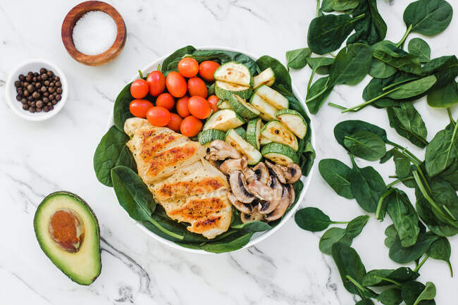 From above cherry tomatoes placed inside bowl of roasted chicken and zucchini with mushrooms on spinach leaves near half avocado and spices — Stock Photo