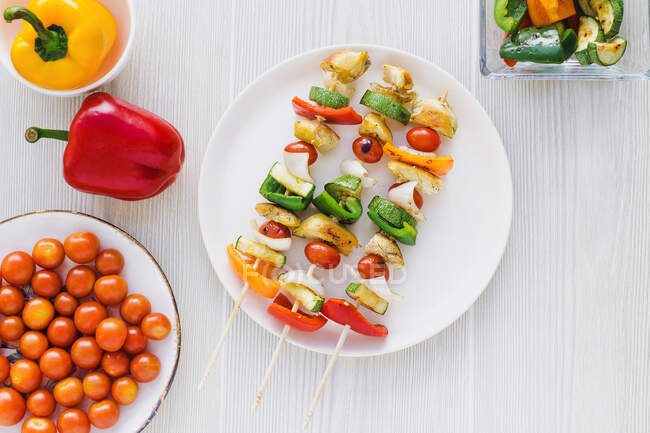 From above chicken skewers with pepper placed on plate near cherry tomatoes and roasted zucchini — Stock Photo
